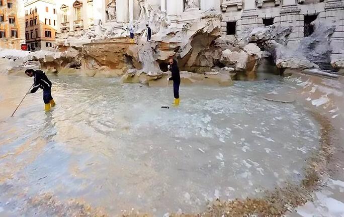 Рабочие достают монеты из фонтана